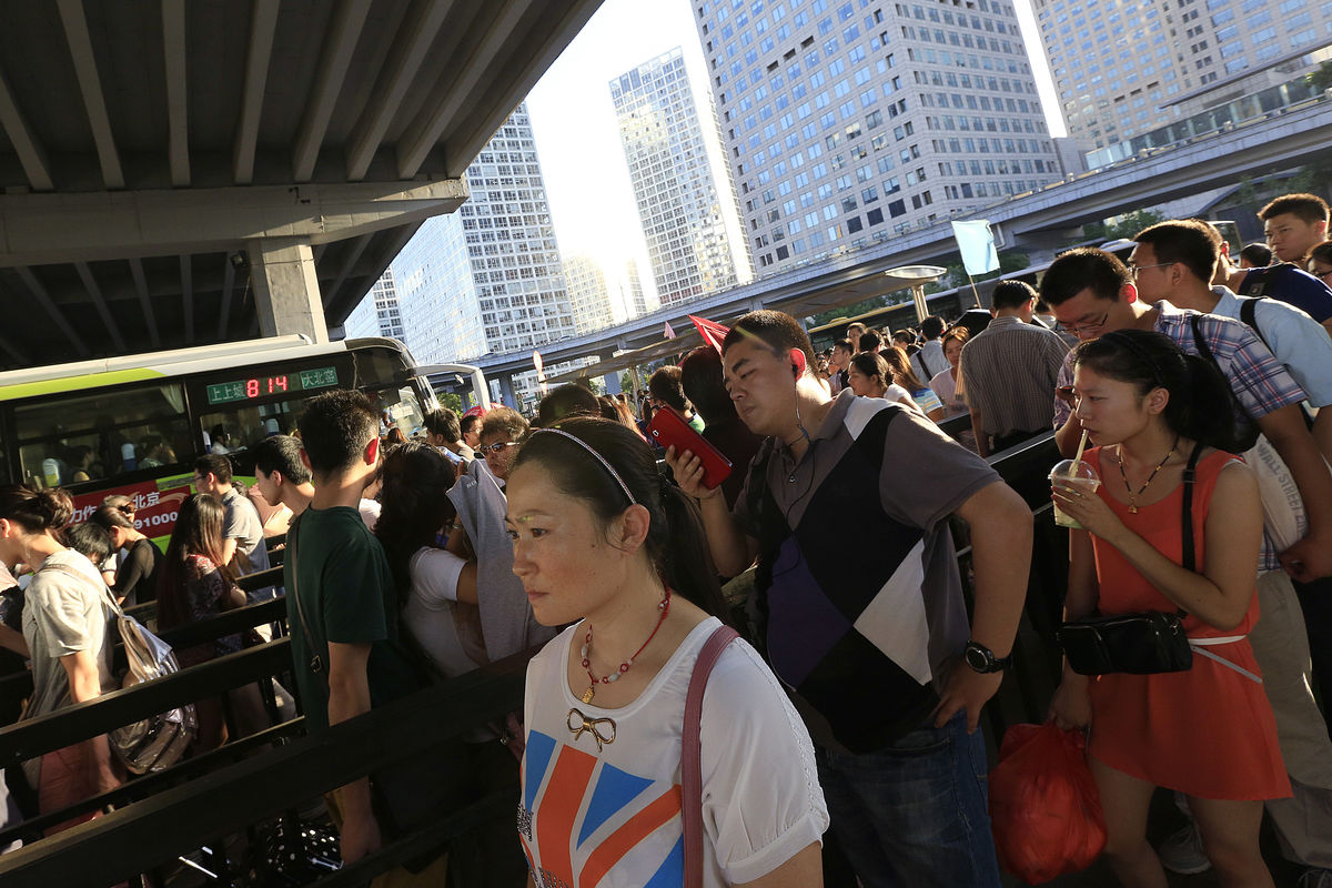 Commuters wait for buses in the central business district of Beijing, China.